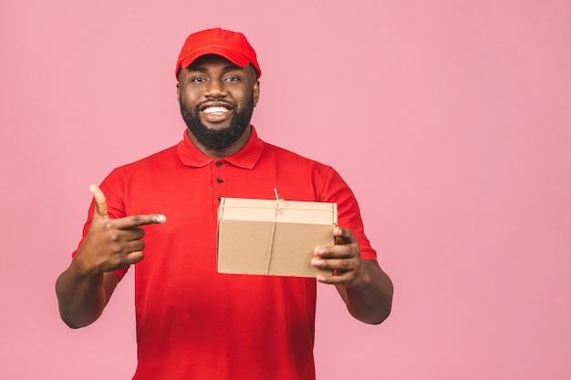 配信コンセプト。ピンクの背景に分離された小包を運ぶアフリカ系アメリカ人の配達黒人男性。
