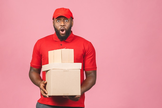 Delivery concept. african american delivery black man carrying parcel isolated over pink background.