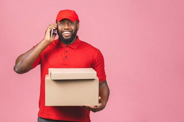 Delivery concept. african american delivery black man carrying parcel. using phone.