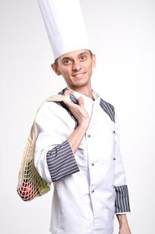 Концепция доставки. шеф-повар приносит продукты. свежие овощи и фрукты на эко авоське на белом фоне. здоровый образ жизни. никаких отходов.