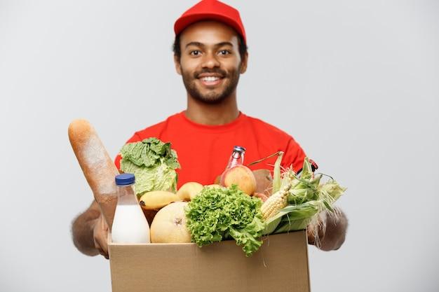 배달 개념-식료품 음식 및 저장소에서 음료의 패키지 상자를 들고 잘 생긴 흑인 배달 남자. 회색 스튜디오 배경에 고립. 공간을 복사하십시오.