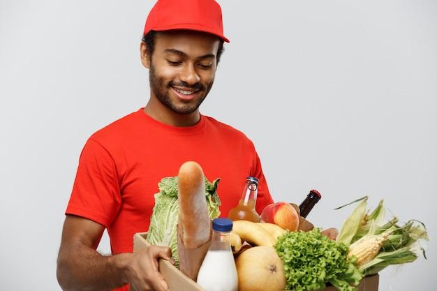 Концепция доставки - красивый афро-американских доставки человек, проведение пакет ящик продуктовых продуктов и напитков из магазина. изолированные на фоне серой студии. копирование пространства.