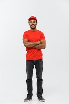 Concetto di consegna - bello uomo di consegna africano americano attraversato le braccia oltre isolato su sfondo grigio studio. copia spazio.