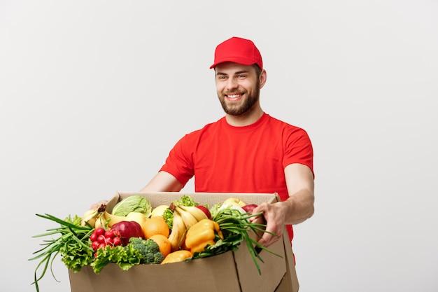 配達の概念:食料品の箱で赤い制服を着たハンサムな白人の食料品配達宅配便男