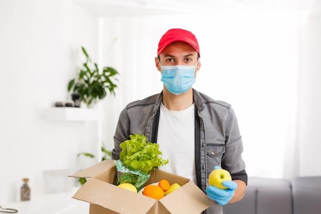 配達の概念:新鮮な果物と野菜の食料品箱を持つハンサムな白人食料品配達宅配便の男