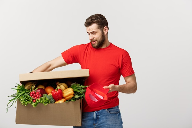配信の概念:ハンサムな配達人は灰色で分離された重い食料品の箱を保持しています。