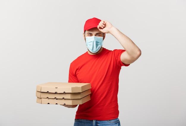 配信の概念:ピザの箱を保持しているキャップと赤い制服を着たハンサムなピザ配達人宅配便。白で隔離されます。