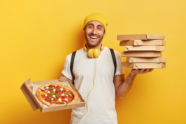 Delivery concept. man pizza dealer holds stack on cardboard boxes, shows tasty fast food in opened container, works as courier, wears yellow hat and white t shirt, uses headphones for listening audio.