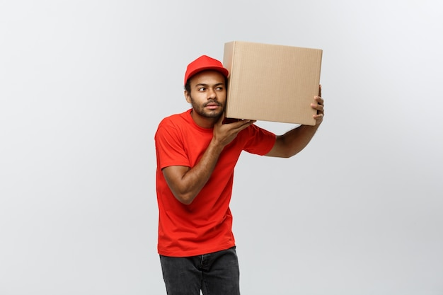 Delivery concept - portrait of curious african american delivery man listen inside a box package. isolated on grey studio background. copy space.
