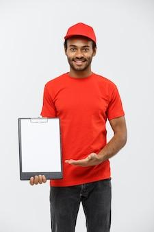 Concetto di consegna - ritratto di bello uomo di consegna africano o corriere che mostra un modulo di documento di conferma per firmare. isolato su sfondo grigio dello studio. copia spazio.