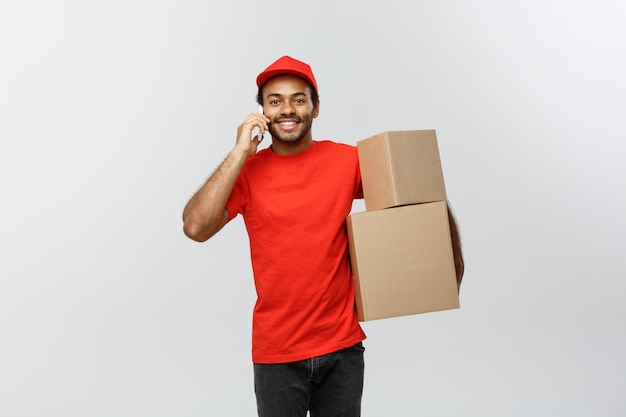 Delivery concept - portrait of handsome african american delivery man or courier showing tablet on you to check the order. isolated on grey studio background. copy space.
