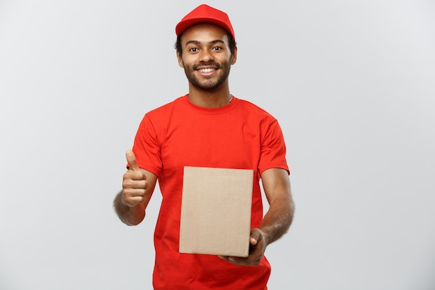 Delivery concept - portrait of happy african american delivery man holding a box package and showing thumps up. isolated on grey studio background. copy space.