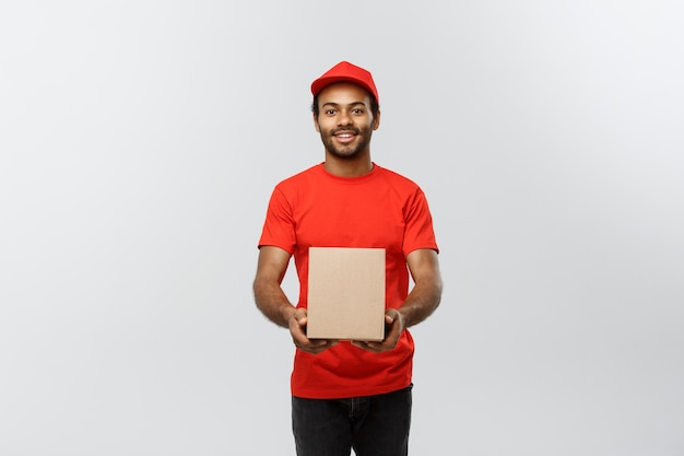 Delivery concept - portrait of happy african american delivery man in red cloth holding a box package. isolated on grey studio background. copy space.