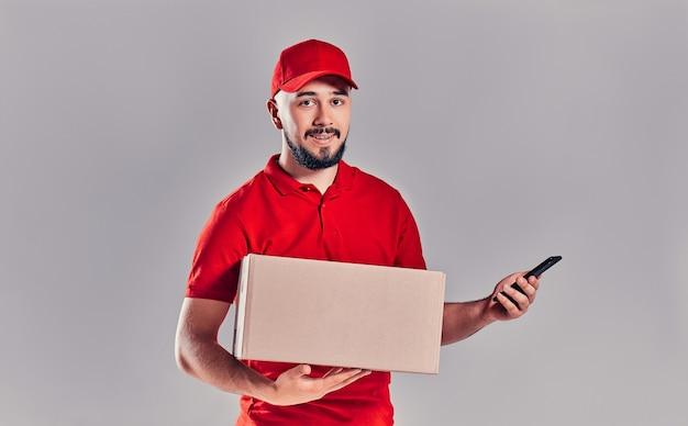 배달 개념 - 주문을 확인하기 위해 휴대폰을 보여주는 상자가 있는 잘생긴 백인 배달원 또는 택배의 초상화. 회색 스튜디오 배경에 고립. 복사 공간.