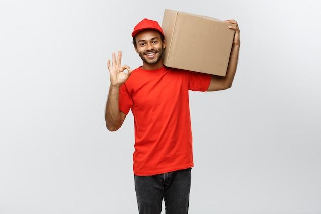 배달 개념-상자 패키지를 잡고 thumps를 보여주는 행복 한 아프리카 계 미국인 배달 남자의 초상화. 회색 스튜디오 배경에 고립. 공간을 복사하십시오.