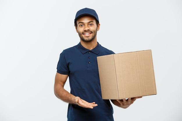 배달 개념-상자 패키지를 들고 빨간 천으로 행복 아프리카 계 미국인 배달 남자의 초상화. 회색 스튜디오 배경에 고립. 공간을 복사하십시오.