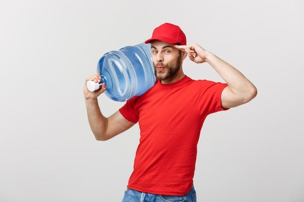 Концепция доставки: портрет улыбающегося курьера по доставке бутилированной воды в красной футболке