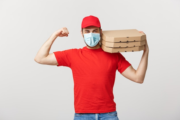 Delivery concept - portrait of strong handsome delivery man flexing his muscle and holding pizza box packages.