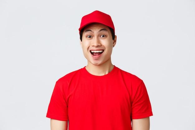 Доставка, бесконтактные заказы и концепция покупок. взволнованный курьер в красной форменной кепке и футболке, курьер улыбается, доволен, смотрит в камеру с энтузиазмом, рекламирует службу перевозчика, серый фон