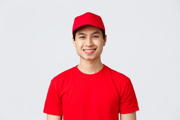 Доставка, бесконтактные заказы и концепция покупок. улыбающийся приятный сотрудник службы доставки, одетый в форменную красную кепку и футболку, бодро смотрит в камеру, помогает покупателю, курьер передает товар.