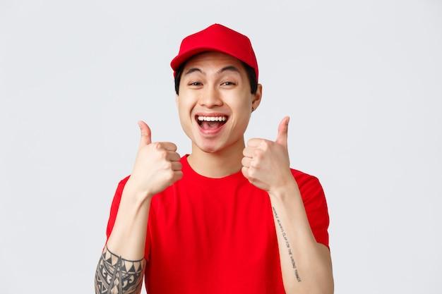 Доставка, бесконтактные заказы и концепция покупок. поддерживающий жизнерадостный молодой азиатский курьер в красной форменной кепке и футболке, одобрительно показывает большие пальцы, рекомендую доставить услуги, серый фон