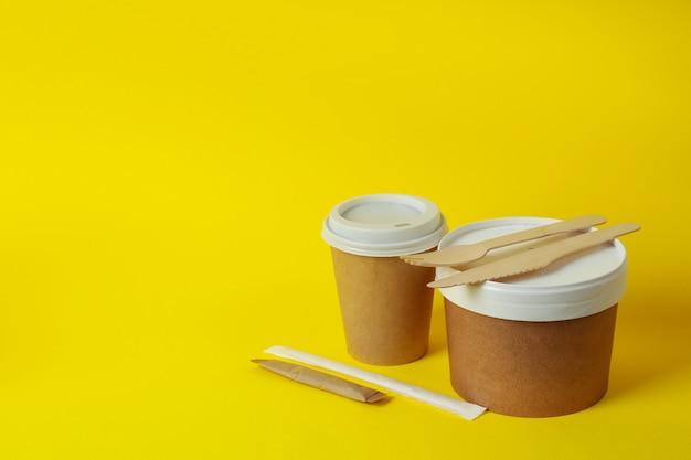 Контейнеры для доставки еды на вынос на желтой поверхности