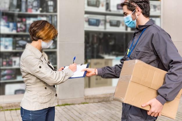 택배 택배가 여성에게 상자를 배달합니다. 여자는 패키지에 서명