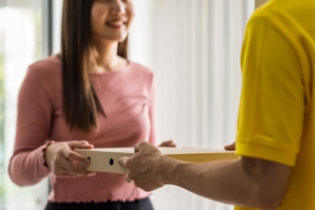 宅配業者の手は、オフィスで笑顔のビジネスウーマンにピザ料理を届けます