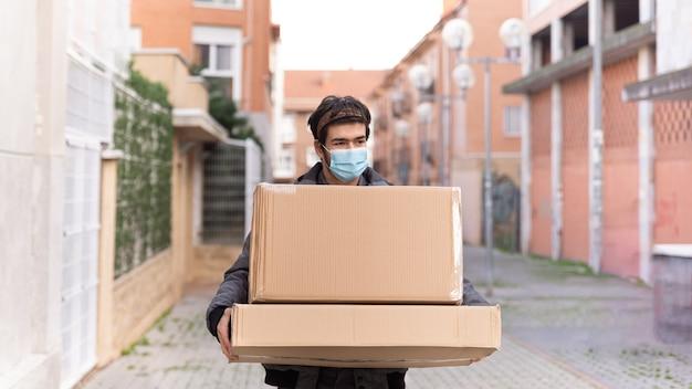 그의 팔에 두 개의 상자를 들고 거리를 걷는 배달 택배