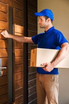 당신의 문에 직접 배달합니다. 집 문을 두드리는 동안 골판지 상자를 들고 잘 생긴 젊은 배달 남자