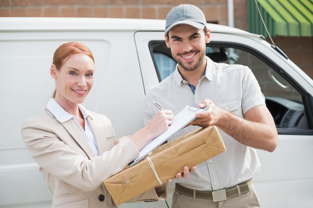 Delivery driver handing parcel to customer outside van outside the warehouse
