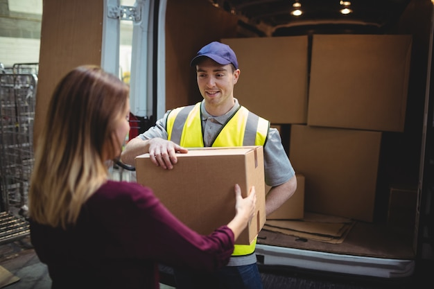 Delivery driver handing parcel to customer outside van in warehouse