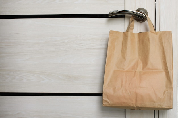 Delivery during the quarantine. shopping bag with merchandise, goods and food is hanging at the front door, neighborhood