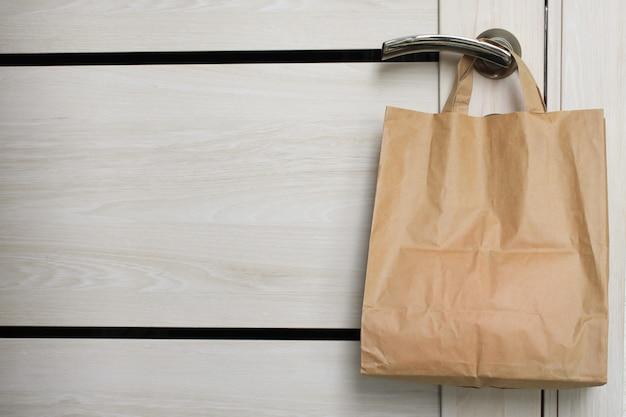 Доставка во время карантина. сумка с товарами, товарами и едой висит на входной двери, окрестности