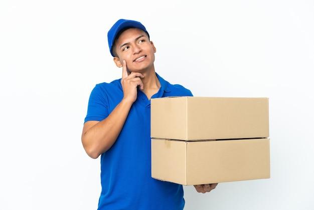 Эквадорский человек доставки, изолированные на белом фоне, думая об идее, глядя вверх
