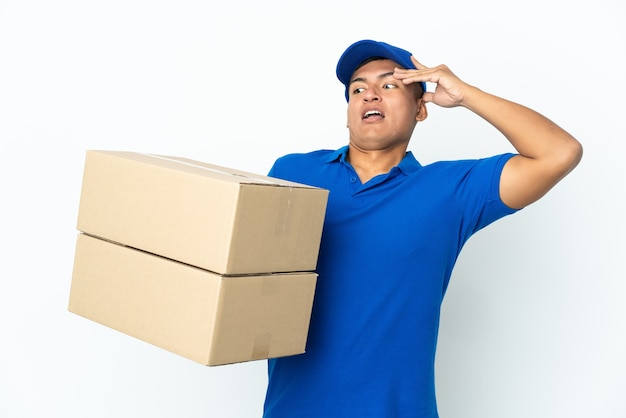 Delivery ecuadorian man isolated on white background doing surprise gesture while looking to the side