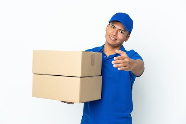 Delivery ecuadorian man isolated on white background shaking hands for closing a good deal