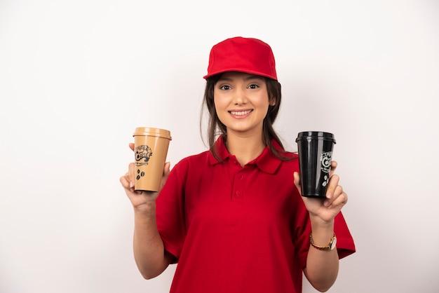 Donna dipendente di consegna in berretto rosso tenendo tazze di caffè su sfondo bianco.