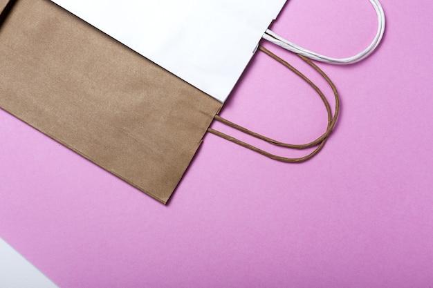 Доставка бумажных пакетов быстрого питания экологичная пищевая упаковка на цветном фоне. пищевая эко-упаковка из переработанной крафт-бумаги