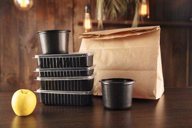 Концепция доставки еды. бумажные пакеты, зеленое яблоко и черные контейнеры с едой на столе.