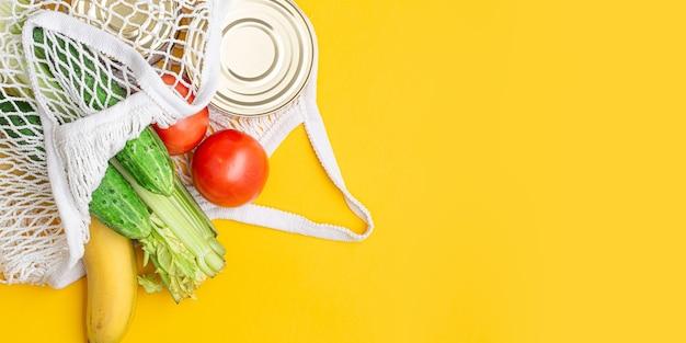 配達食品。黄色の背景にストリングバッグに入った食品。缶詰、トマト、きゅうり、バナナ。寄付、コロナウイルス。検疫のための食料。コピースペース。長く広いバナー