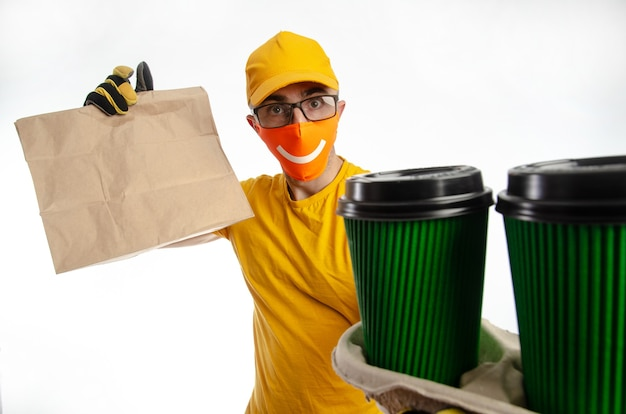 Delivery of food and goods under quarantine, the guy delivering packages in a virus-proof mask, the courier with coffee and pizza