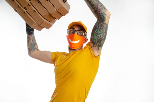 Delivery of food and goods under quarantine, the guy delivering packages in a virus-proof mask, the courier with pizza