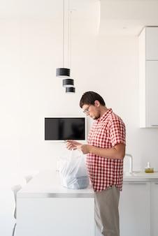 배달 음식, 집으로 제품. 쇼핑 및 건강 식품 개념입니다. 현대 부엌에서 음식 배달과 함께 일회용 비닐 봉투를 들고 빨간 격자 무늬 셔츠에 젊은 남자