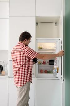 Доставка еды, продуктов на дом. шоппинг и концепция здорового питания. молодой человек в красной клетчатой рубашке держит одноразовые пластиковые коробки с едой и кладет их в холодильник
