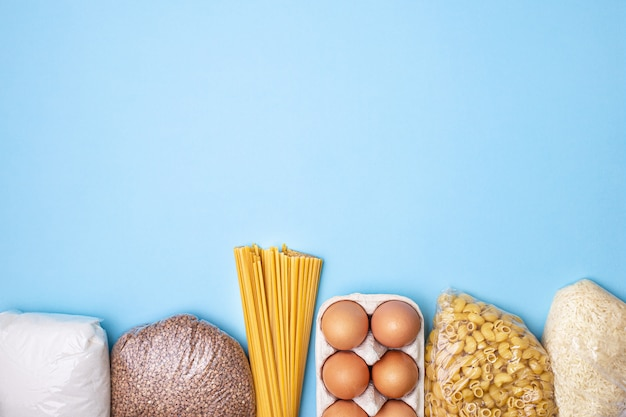 Delivery food. rice, buckwheat, pasta, canned food, sugar on blue background.