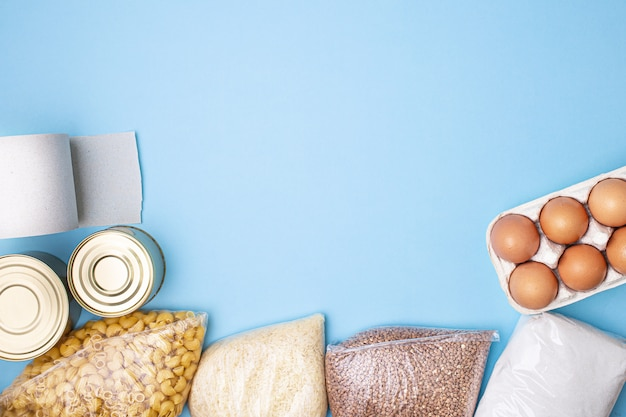 Delivery food. rice, buckwheat, pasta, canned food, sugar, toilet paper on blue background.