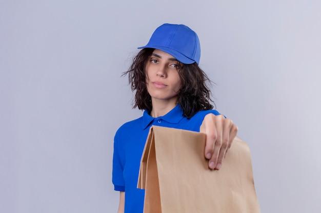 Ragazza delle consegne in uniforme blu e cappuccio che dà il pacchetto di carta al cliente con la faccia seria su bianco isolato
