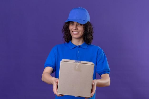 Ragazza di consegna in uniforme blu e pacchetto della scatola della tenuta del cappuccio che sorride amichevole, positivo e felice che si leva in piedi sulla porpora isolata