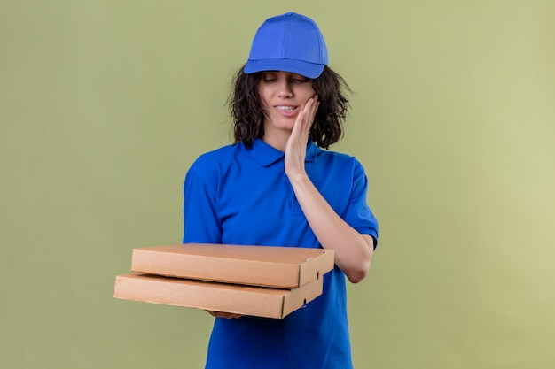Delivery girl in blue uniform and cap holding pizza boxes biting lip with hungry expression smiling standing on isolated olive color